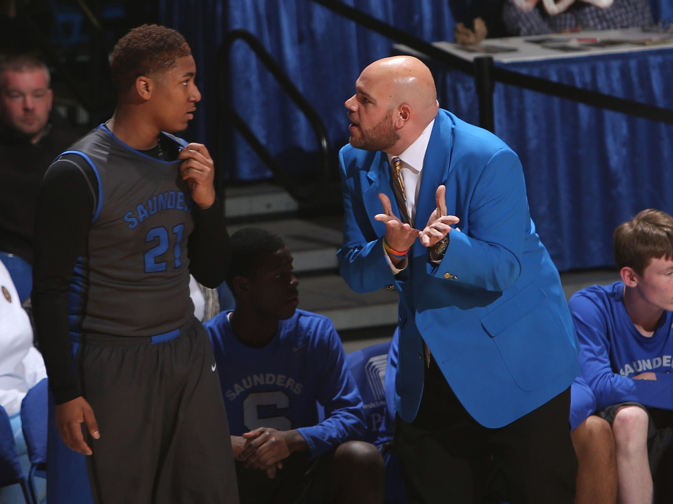 Anthony Nicodemo, right, speaks to a player during a game. Nicodemo is one of few openly gay high school coaches.