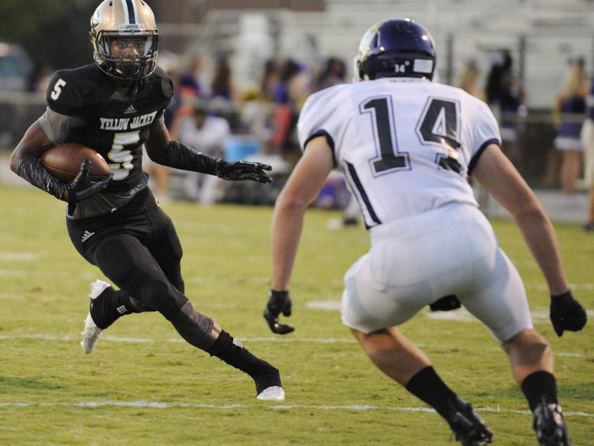Greer High senior Troy Pride (5) sizes up an Emerald defender in the open field during the Yellow Jackets' 39-20 victory at Dooley Field Sept. 18.