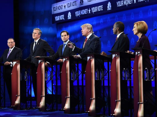 Republican presidential hopefuls look on during the