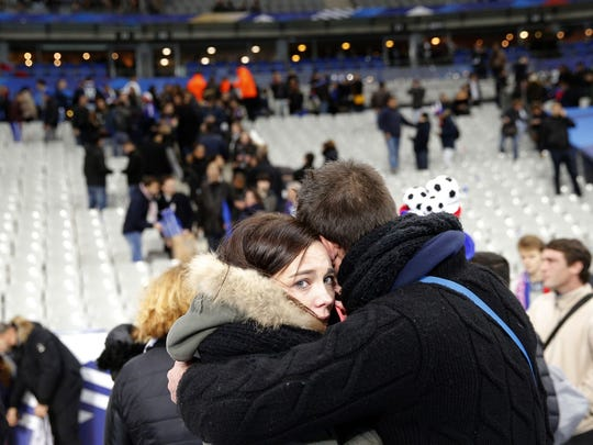 Spectators embrace each other as they stand on the