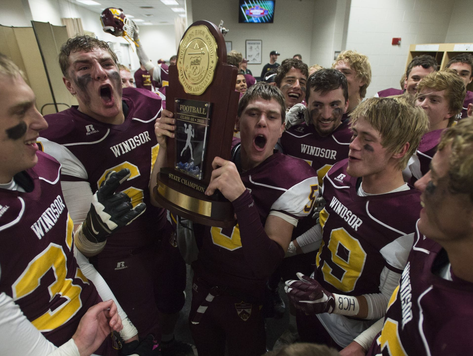 The Windsor High School football team celebrates with the Class 4A trophy at Sports Authority Field at Mile High.