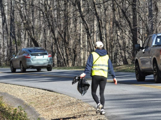 A volunteer cleans up trash in the Asheville corridor of the Blue Ridge Parkway Thursday. With an extra 1 million visitors last year, but a flat budget and same number of staff, the parkway relies more heavily on volunteers to keep the park clean and maintained.