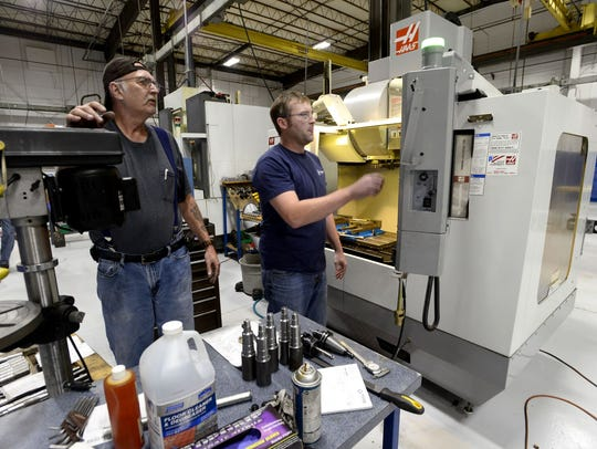 Workers at TPR Systems Inc. machine parts on high-tech