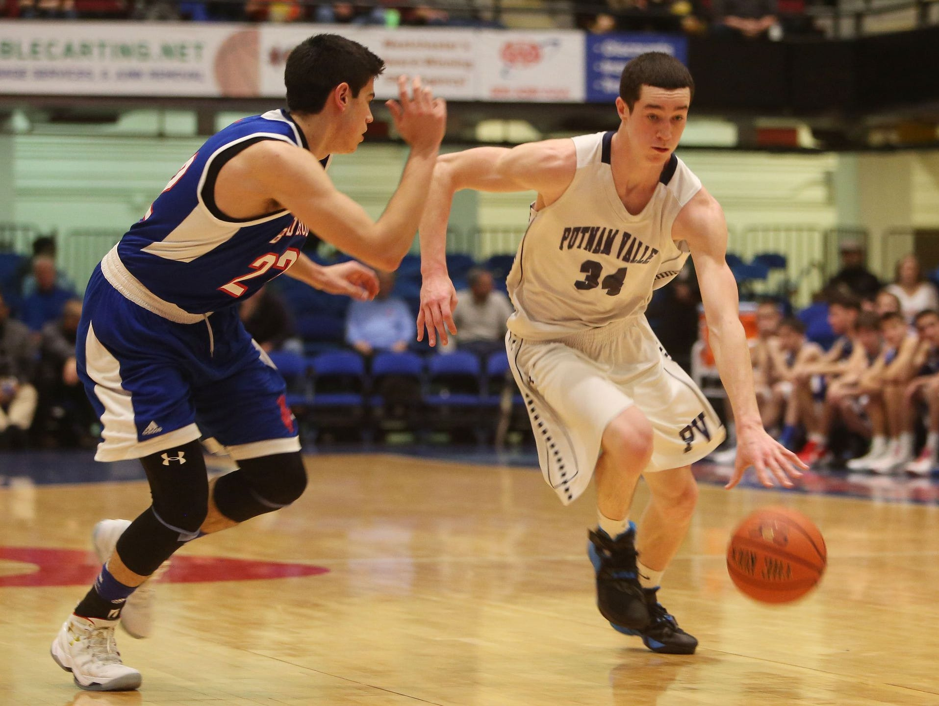 Putnam Valley's Joe Spinola (34) drives to the basket in front of Blind Brook's Austin Levitt (22) during the boys Class B semifinal at the Westchester County Center in White Plains Feb. 24, 2016. Putnam Valley won the game 48-39.