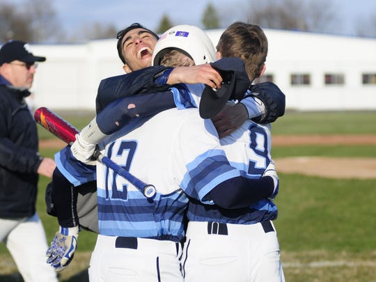 Stefan Fenwick smiles as he celebrates Richmond's walk-off win with Chase Churchill (9) and Connor Margosian (12) on April 13, 2016 at Richmond High School.