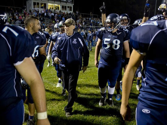 Richmond players walk with coach John Kocher -- the 2015 Sportsperson of the Year -- after a football game