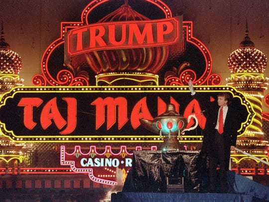 Donald Trump stands next to a genie lamp as the lights of the Trump Taj Mahal Casino Resort light up the evening sky marking the grand opening of the venture in Atlantic City on April 5, 1990/