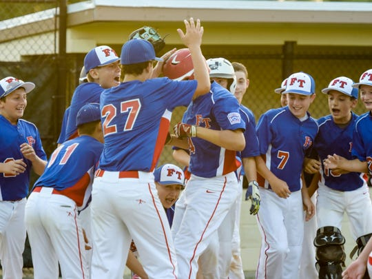 The Freehold Township team celebrates a home run by Jonathan Olik