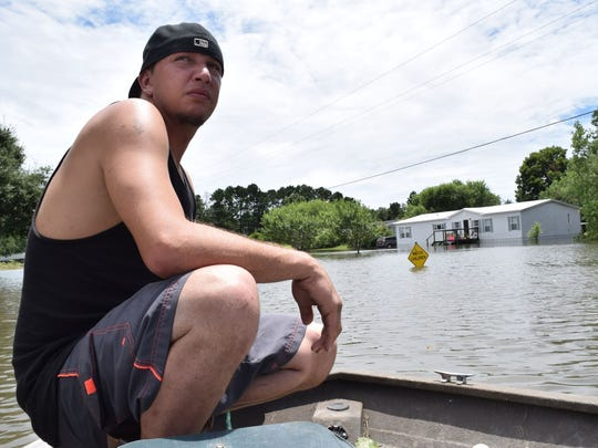An unidentified man sits on a boat amid floodwaters