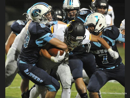 The Redwood defense makes a tackle against Tulare Union during their football game at Giant Chevrolet-Cadillac Mineral King Bowl on Friday, September 9, 2016.