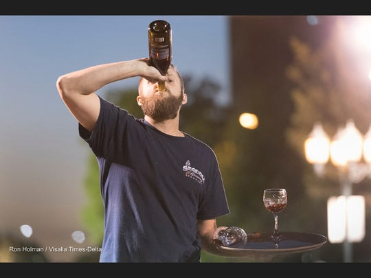 Cole Ledbetter from Sequoia Brewing Company takes a dink after placing 2nd in his heat during the Annual Visalia Waiters Race in Downtown Visalia on Thursday, September 22, 2016.