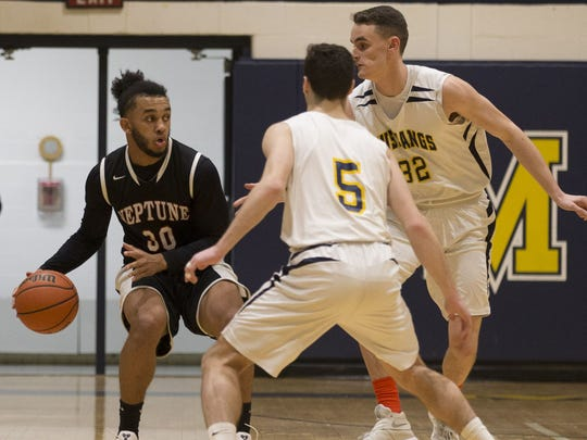 Neptune's Jules Calhoun (left) is guarded by Marlboro's P.J. Ringel (5) and Daniel Weiss (32) in a Class A North game in Jan.  2017