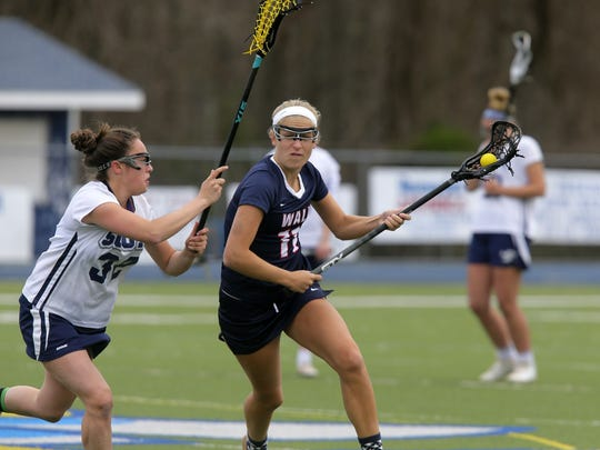 Middletown South's Roberta Montes (left) defends Wall's Becky Kurfehs during a game at Middletown South on April 13, 2017. The Crimson Knights won 16-9 to end a four-game losing streak.