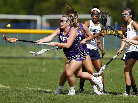 Rumson-Fair Haven's Caitie Clark (#22) reaches for the ball ahead of Freehold Township defenders during their game at Freehold Township High School Monday, May 1, 2017  Thomas P. Costello