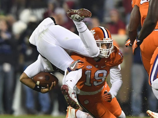 Clemson's Tanner Muse (19) upends a South Carolina player last year during the Tigers' win in Death Valley.
