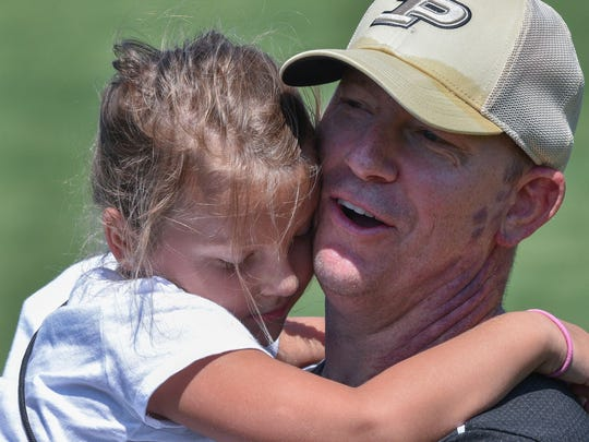 Purdue head coach Jeff Brohm holds his daughter, Brooke, at practice