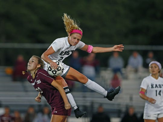 Toms River East's Jillian Conklin slides off the back of Toms River South's Stephanie Tomkawich as the two battle for a ball during first half action. Toms River South vs Toms River East Girls Soccer in Toms River on October 3, 2017  Peter Ackerman