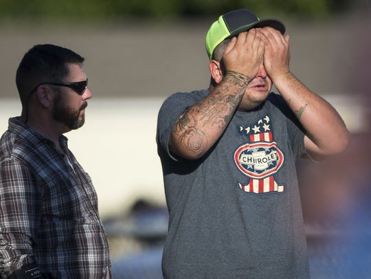 A man wipes his eyes after a deadly shooting at the