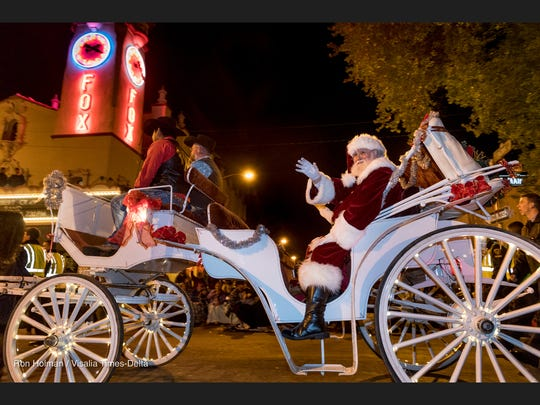 Santa Claus waves to the crowd along Main Street during Visalia's 72nd Candy Cane Lane Parade on November 27, 2017.