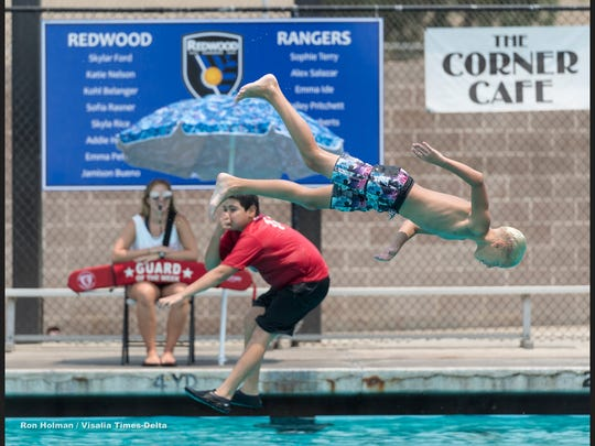 Lifeguard Mary Akin watches Caleb Vilhauer, 12, left, and Leo Barrios, 11, dive during public swim at Redwood Community Pool on Friday, July 27, 2018.