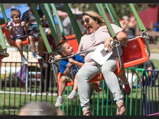 Adrian Gonzales, 4, left and his mother Melissa Gonzales of Tulare ride the Lolli Swinger as the Tulare County Fair kicked off Wednesday, September 12, 2018 with Kids Day right after the morning parade.