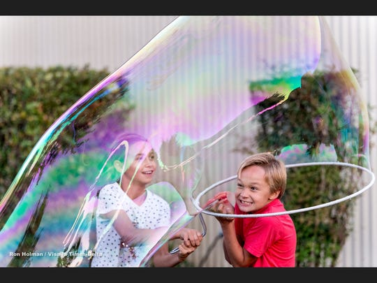 Marie Van Ryn, 9, left, and her brother Jack Van Ryn, 8, of Tulare plays with soap bubbles at the Tulare County Fair on Thursday, September 13, 2018.