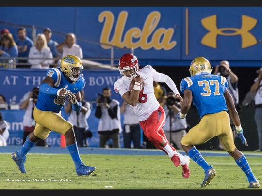 Fresno State quarterback Marcus McMaryion runs between