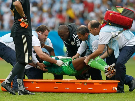 Nigeria's Michael Babatunde is lifted from the pitch before being taken off the field during the group F World Cup soccer match against Argentina at the Estadio Beira-Rio in Porto Alegre, Brazil, Wednesday, June 25, 2014. (AP Photo/Jon Super)