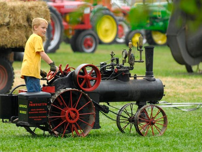 Geordi Moffatt, of Wyoming, Ontario, rides on a small tractor being pulled by a truck, Aug. 24, during the St. Clair County Farm Museum's Steam Show and Old Fashion Harvest Days at Goodells County Park.