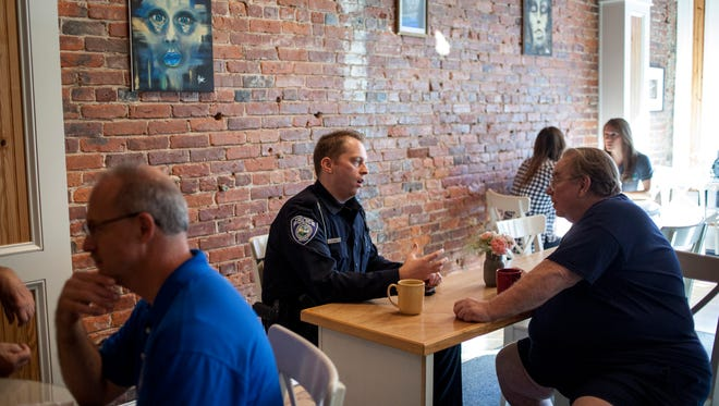 Port Huron Police Officer Patrick Eash chats with Dale Jurk, of Port Huron, during Coffee with a Cop Friday, Oct. 7, 2016 at Kate's Downtown in Port Huron.