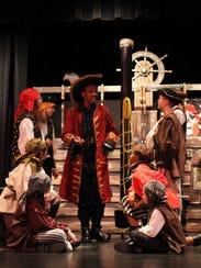 Captain Hook (center, played by Julien Johnson) speaks