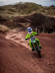 Lawrence Limtiaco, 12, churns up some dirt.