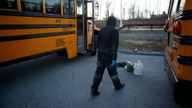 A worker with Royal Coach Buses cleans one of the buses that were vandalized behind Somers High School over the weekend, forcing a district wide school closure on Monday.