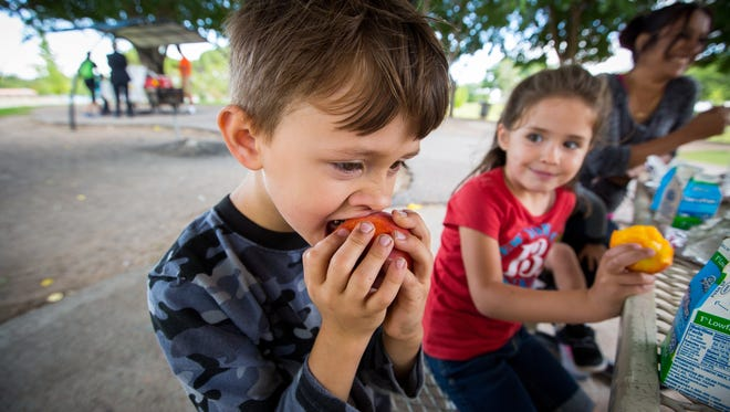 5-year-old Seth Potts bites into a peach provided as part of a free lunch by Families and Youth, Inc. at Young Park while 5-year-old Vivian Trivizo looks on, June 1, 2016.