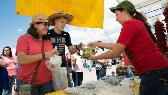 Salazar Produce booth employee Victoria Salazar, right, hands Tim Rudolph, and his fiancé Rita Nogin a bag of roasted green chile, September 3, 2016, during the Hatch Chile Festival.