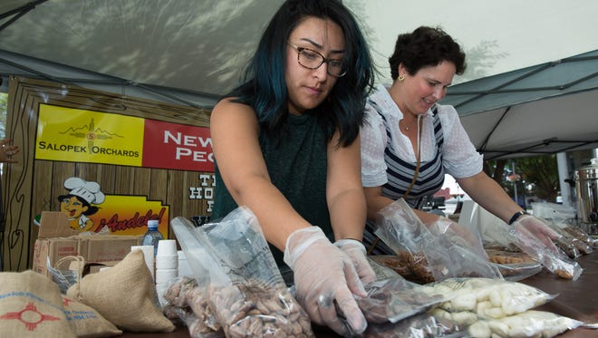 Representatives for Mesilla Valley Store Rachelle Mirabal, left, and Samantha Bustmantes organize pecan coated treats for customers on Saturday, October 8, 2016, during Mesilla's First Annual Pecan Festival.
