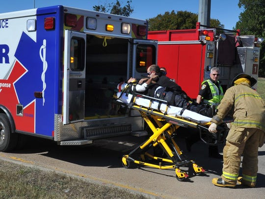 Emergency medical responders load a cyclist who was
