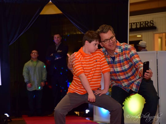 Eddie Craig and Evansville Mayor Lloyd Winnecke pose for a selfie on the runway of the Night of Stars and Styles in this file photo. The event is a fundraiser for SMILE on Down Syndrome. This year's event is Sunday.