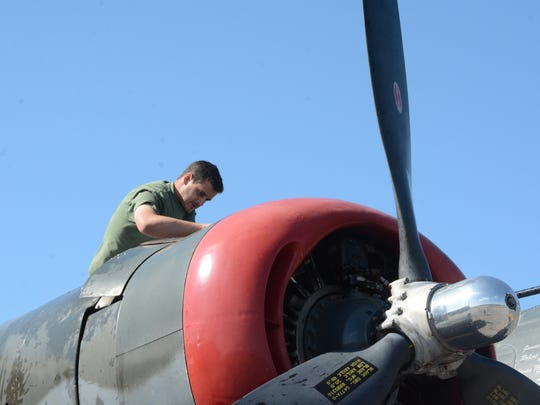 """A pilot works on the B-24J Liberator known as """"Witchcraft"""""""
