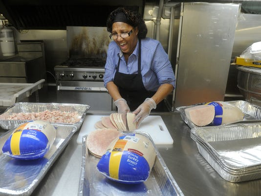 Cecelia Ann Harris, the kitchen manager for Abundant Life Outreach, based in the basement of the New Covenant Community Church in York city, jokes around with staff while preparing dinner on Wednesday, March 11, 2015. The program prepares snacks daily for 1200 children and dinner for 700-800 children throughout twelve city schools. This is for the Salem Square neighborhood story. Jason Plotkin - Daily Record/Sunday News
