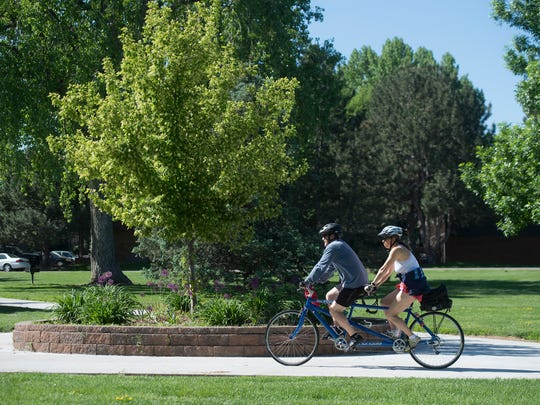 A pair of cyclists ride through Sanborn Park on a tandem bicycle in Greeley on Saturday, May 26, 2018.