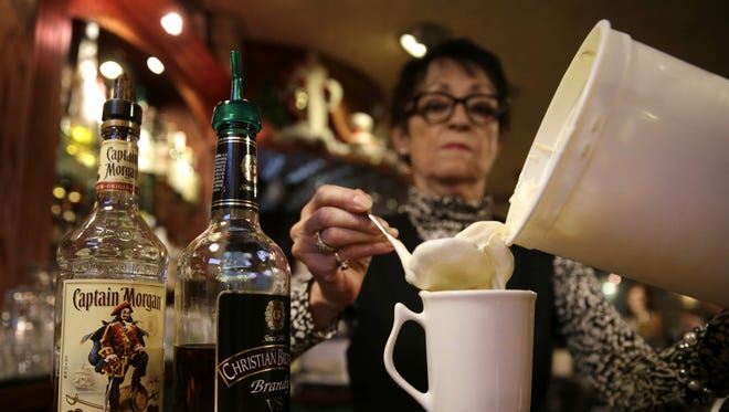 Catherine Cole, a bartender at Mark's East Side, scoops out a spoonful of homemade batter while demonstrating how to make a Tom & Jerry, Dec. 9, 2015, in Appleton. The Tom & Jerrys consists of brandy, Captain Morgan Spiced Rum, homemade batter, hot water, and is topped with nutmeg.