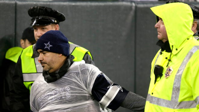A Dallas Cowboys fan is escorted from Lambeau Field in the fourth quarter.