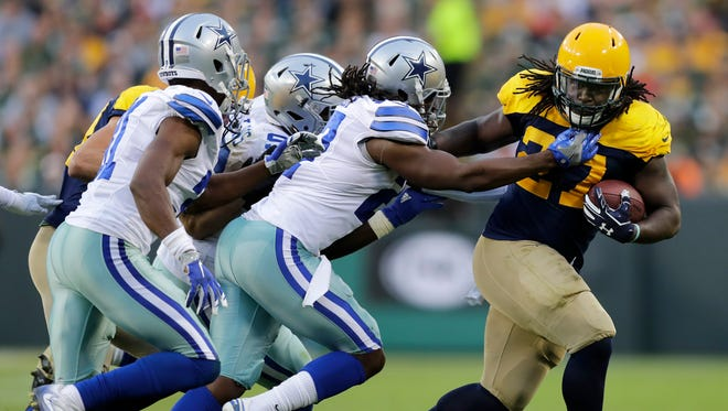 Green Bay Packers running back Eddie Lacy runs for yardage against the Dallas Cowboys defense at Lambeau Field.