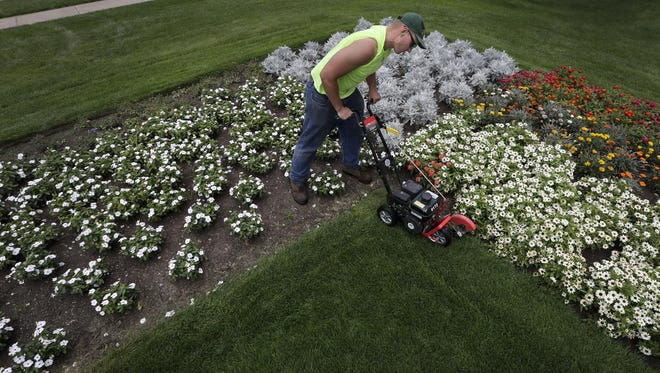 Chris Brunn, a Menasha Parks and Recreation Department employee, edges a garden bed in August at Smith Park in Menasha.