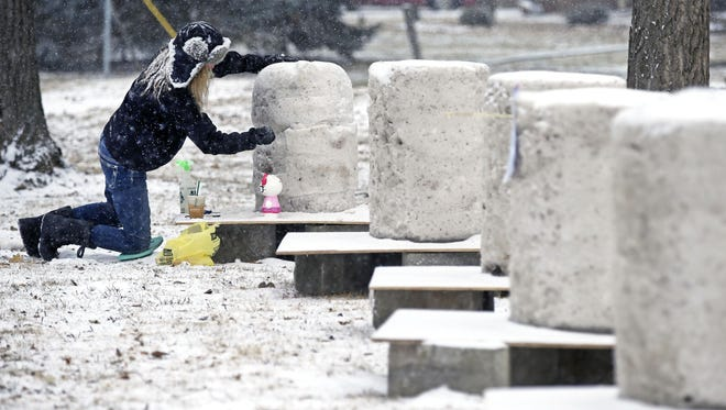 Terese Poeschl of Omro works on what will become a Hello Kitty character as snow carvers begin work while snow falls Feb. 3 during the Smith Park Winter Gala at Smith Park in Menasha.