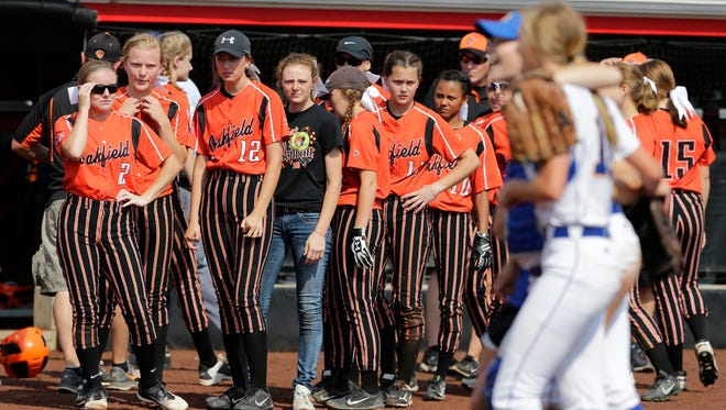 Oakfield's team watches as McDonell Catholic's players celebrate.  Oakfield Oaks played McDonell Catholic in the Division 5 WIAA State Softball Championship at UW-Madison's Goodman Field, June 9, 2018.  McDonell beat Oakfield 5 - 2 in the championship game.