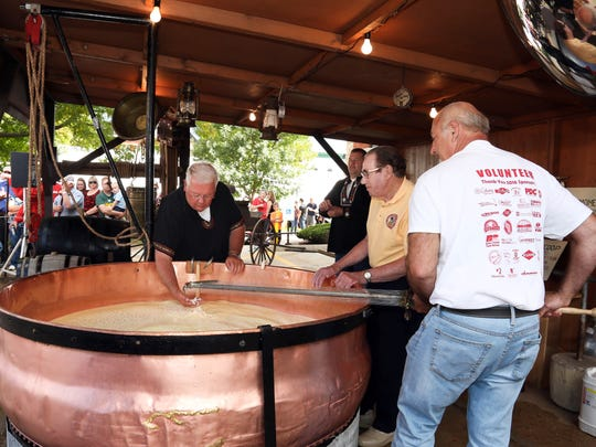 Cheesemakers at Cheese Days in Monroe demonstrate how a wheel of cheese was produced in the old days using a large copper kettle.