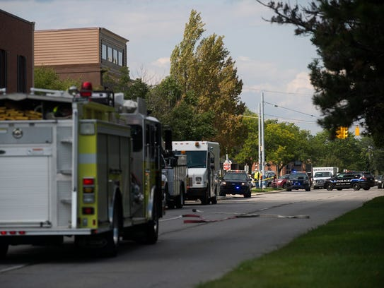 A firetruck, DTE Energy truck and police cars sit on