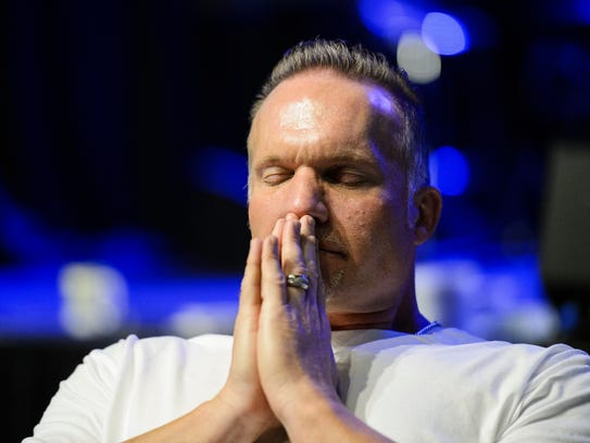 Pastor Ron Carpenter prays before his meal during a